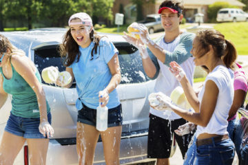 Happy teens playing outside at a car wash. There are girls and guys in their late teens to early twenties. It is summer time and it is warm outside, the teens are wearing shorts, t-shirts, and other summer clothes like baseball hats.