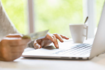 Female buying something on internet with computer and credit card. Garden blur background