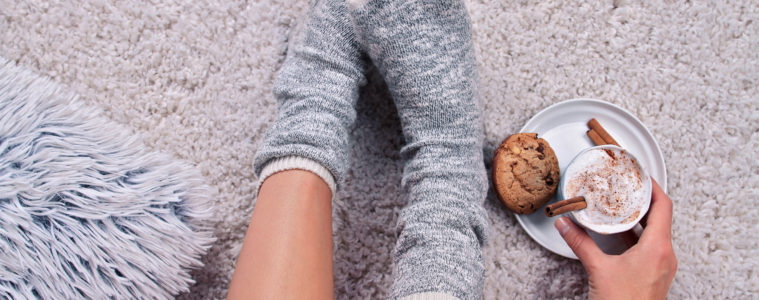 Woman wearing cozy warm wool socks relaxing at home, drinking cacao, winter lazy day concept, top view. Soft, comfy lifestyle.